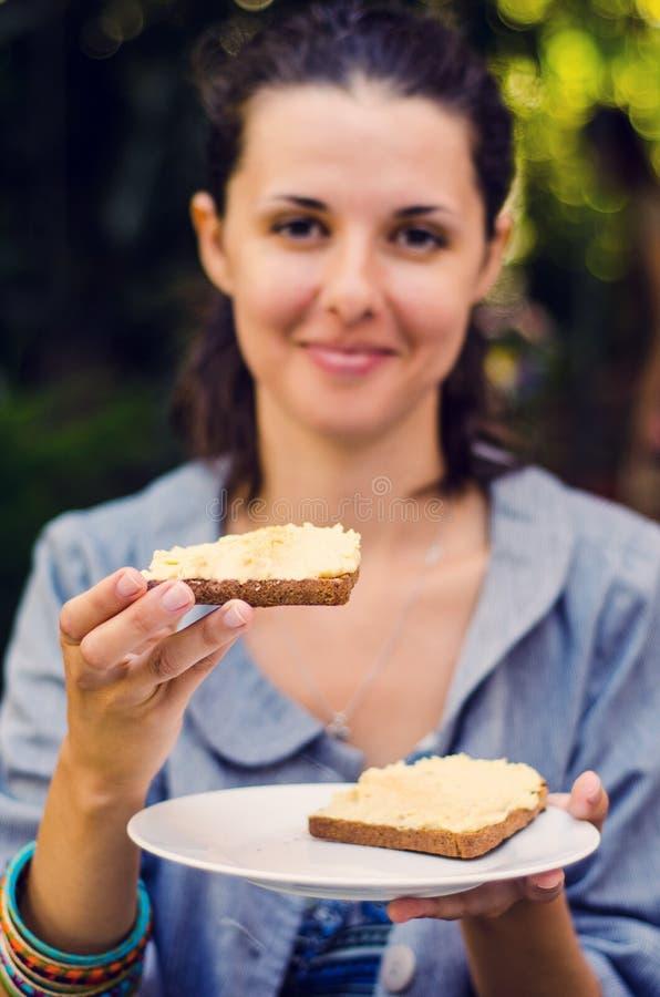 Mulher com sanduíche do hummus fotografia de stock royalty free