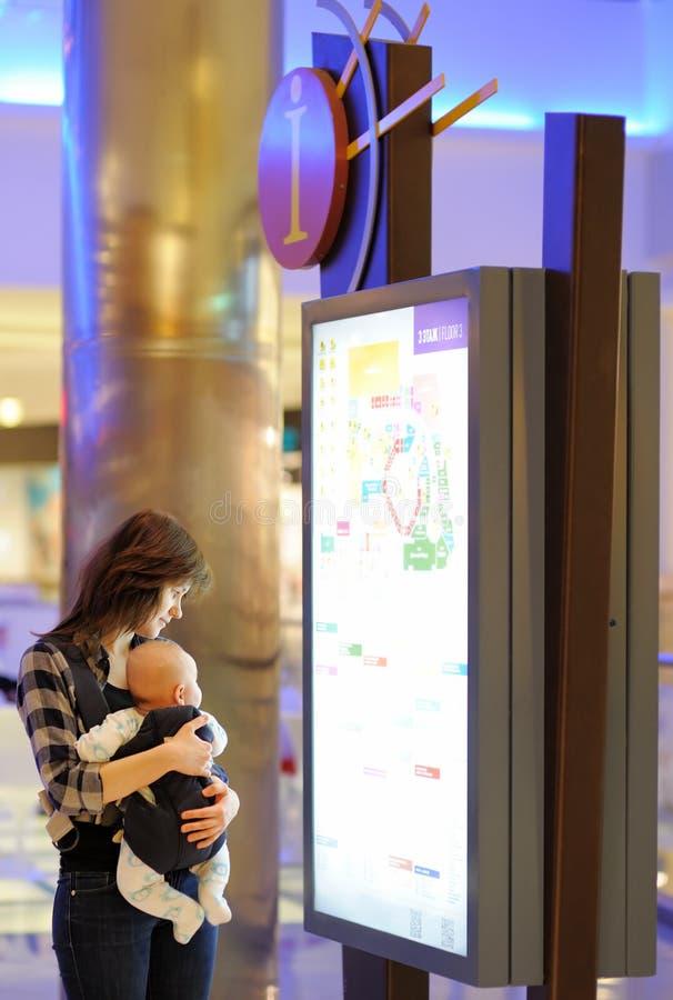 Mulher com seu bebê em um shopping fotografia de stock royalty free