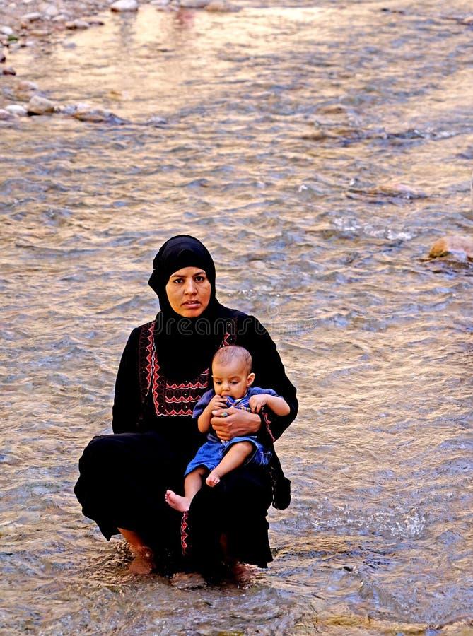 A mulher com seu bebê no rio do Todra gorges em Marrocos