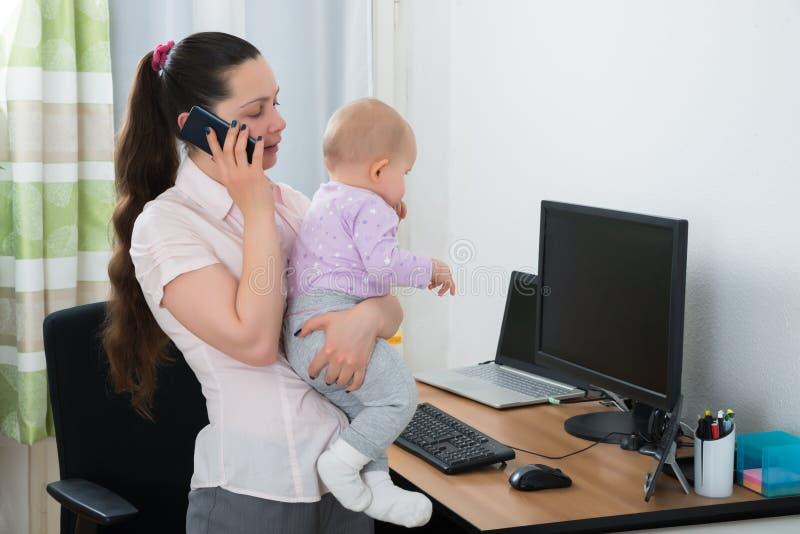 Mulher com seu bebê que fala em Smartphone fotos de stock royalty free