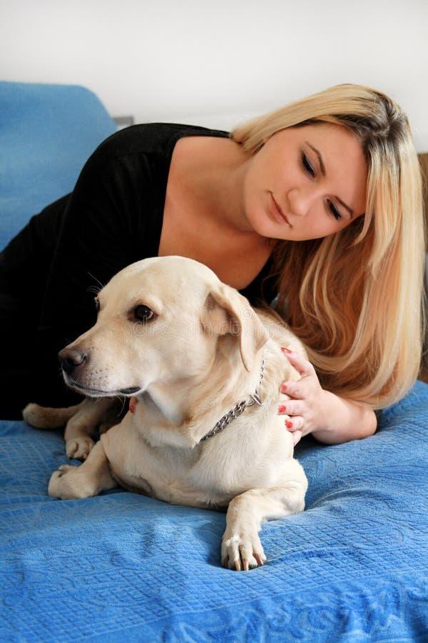 Mulher com seu cão na cama em casa, relaxando no quarto A menina bonita está jogando, junto e trocas de carícias com o cão na cam imagens de stock royalty free