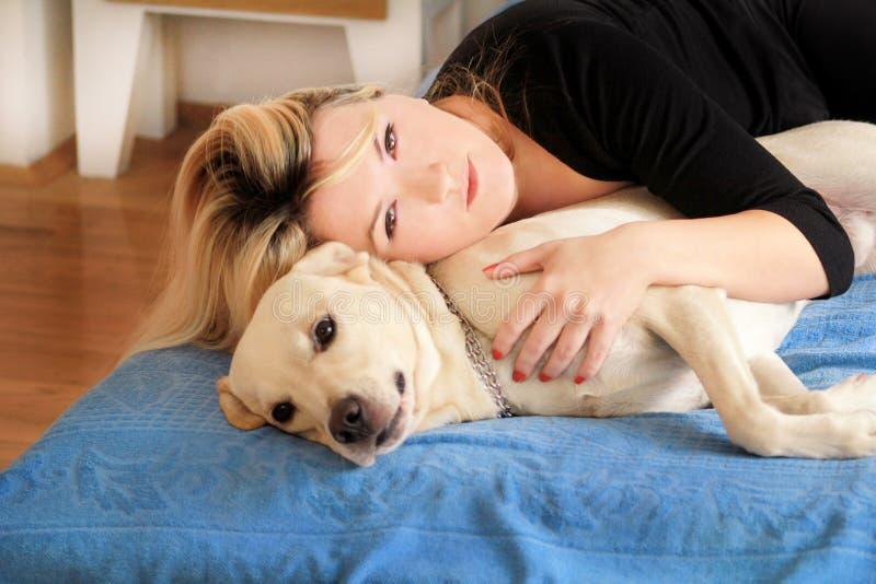 Mulher com seu cão na cama em casa, relaxando no quarto A menina bonita está jogando, junto e trocas de carícias com o cão na cam fotografia de stock royalty free
