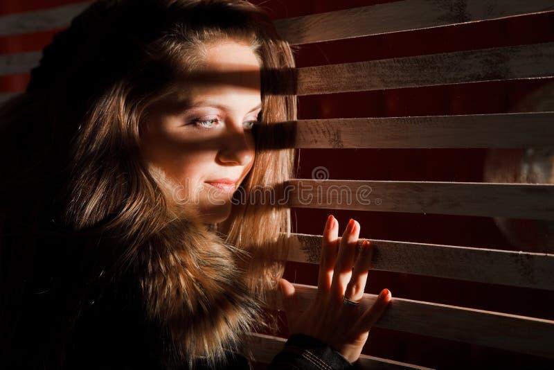 A mulher com seu cabelo olha através das barras. imagens de stock