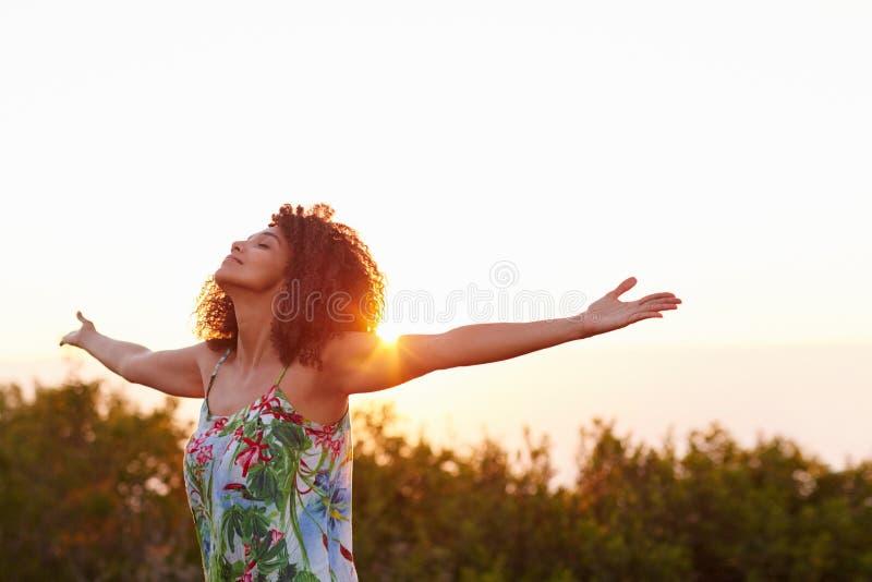 Mulher com seus braços estendido em uma expressão da liberdade foto de stock royalty free