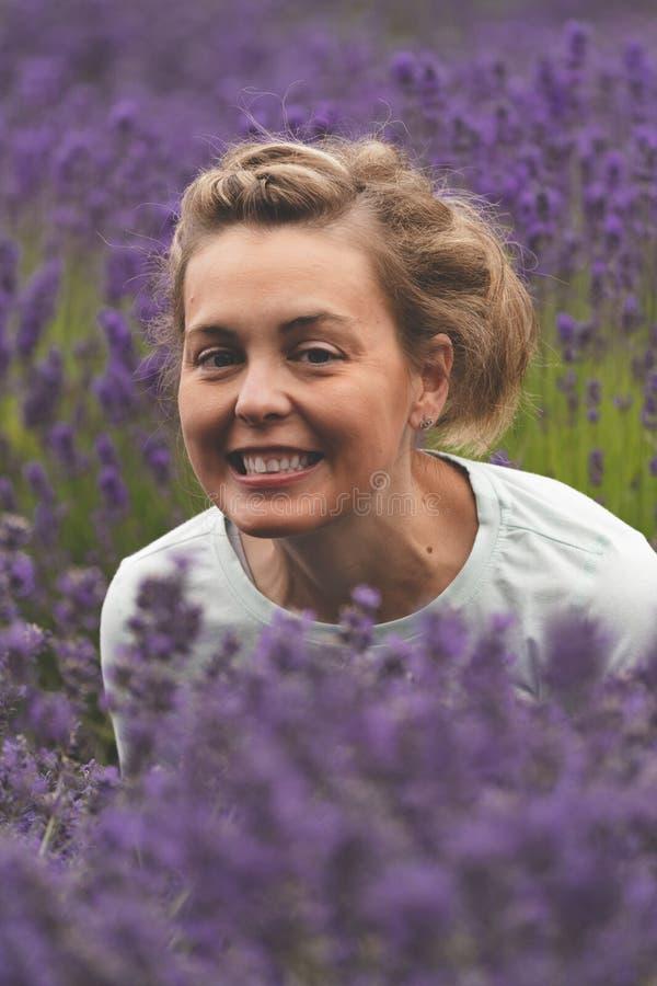Mulher com sorrisos morenos do cabelo ao levantar em um campo de flores da alfazema em Sequim Washington foto de stock