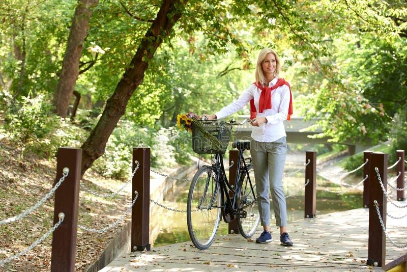 Mulher com sua bicicleta na cidade foto de stock