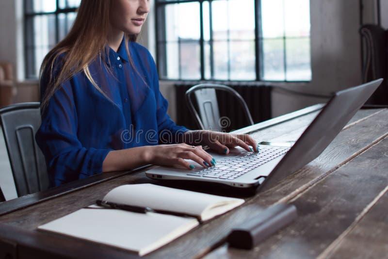 Mulher com suas mãos no teclado do portátil Desenhista que senta-se no worktable com caderno e computador nele foto de stock royalty free