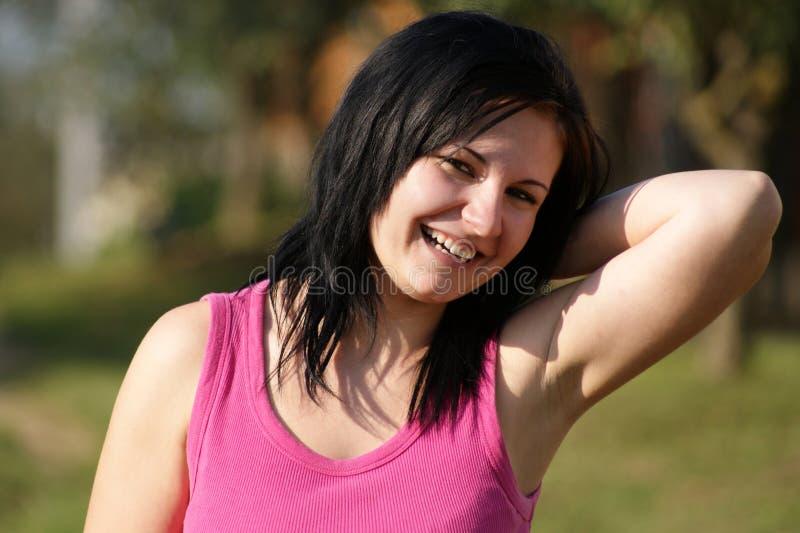 a mulher com t-shirt cor-de-rosa olha no sol imagem de stock royalty free