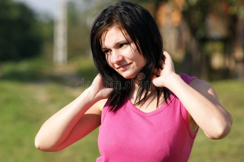a mulher com t-shirt cor-de-rosa olha no sol fotografia de stock royalty free