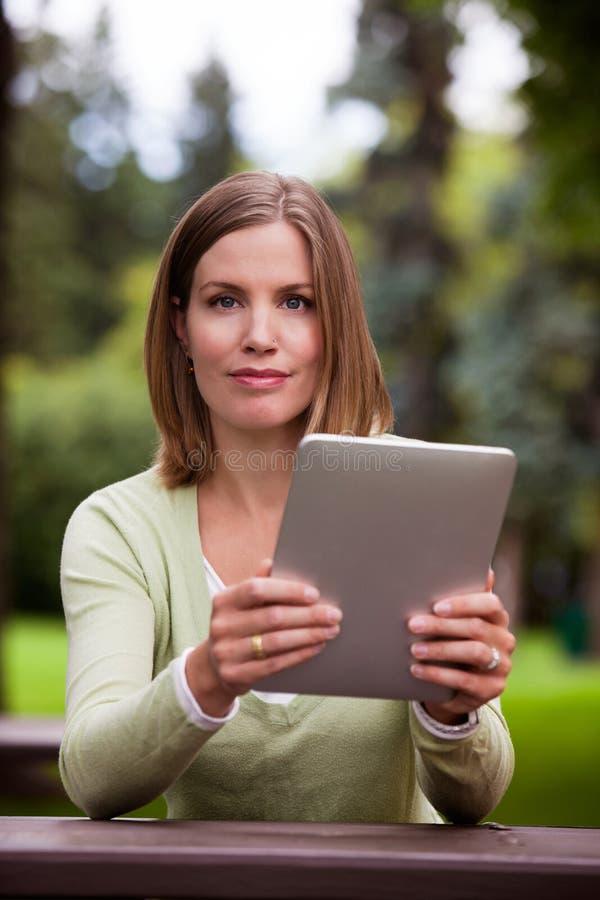 Mulher com tabuleta de Digitas fora fotos de stock