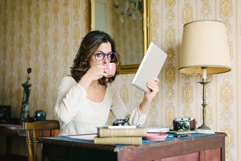 Mulher com a tabuleta digital que trabalha em casa imagens de stock royalty free