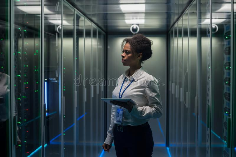 Mulher com tabuleta que diagnostica o hardware do servidor fotografia de stock