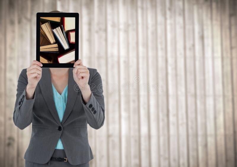 Mulher com a tabuleta que mostra livros eretos contra o painel de madeira obscuro imagem de stock royalty free