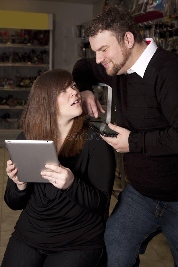Mulher com tabuleta que pede o homem a ajuda imagens de stock royalty free