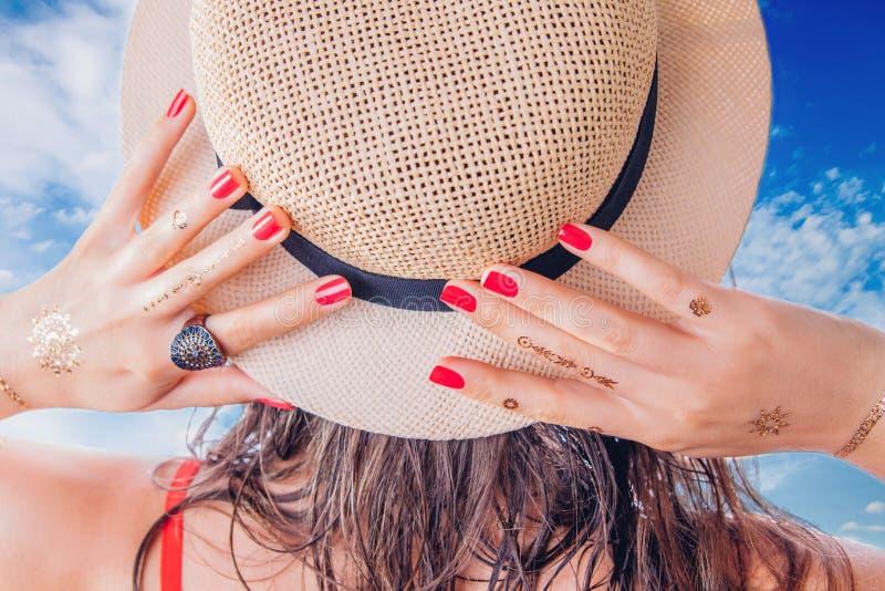 A mulher com tatuagem dourada do mehendi e tratamento de mãos vermelho guarda seu chapéu fotos de stock