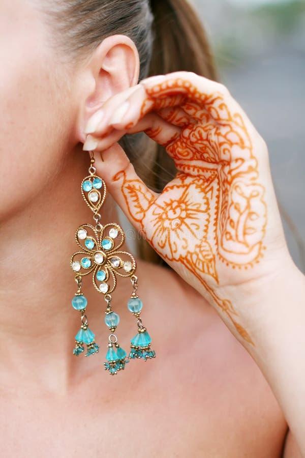 Mulher com tatuagem e brinco do henna imagem de stock