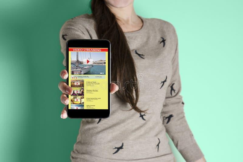 Mulher com telefone à disposição, mostrando fluindo o vídeo imagens de stock royalty free