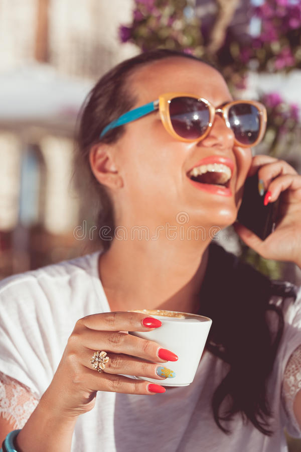 Mulher com telefone celular que aprecia o café no café do passeio fotografia de stock