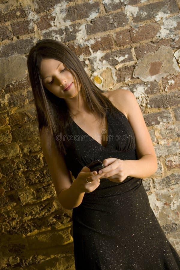 Mulher com telefone de pilha   fotografia de stock royalty free