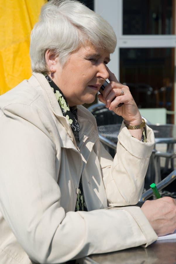 Mulher com telefone de pilha imagem de stock royalty free