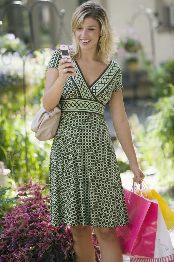 Mulher com telefone de pilha e sacos de compra fotos de stock