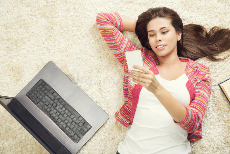 Mulher com telefone e portátil, moça que usa o computador imagens de stock royalty free