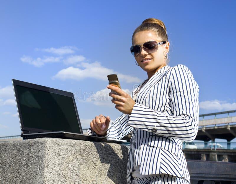 Mulher com telemóvel e portátil fotos de stock royalty free
