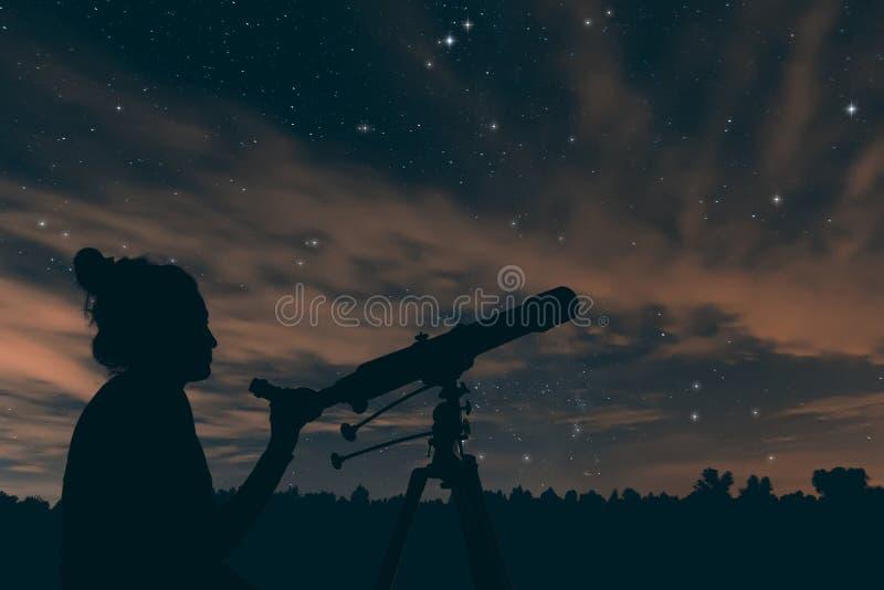 Mulher com telescópio astronômico Céu nocturno foto de stock