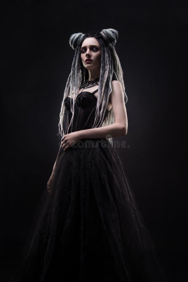 A mulher com teme e vestido gótico preto fotografia de stock royalty free