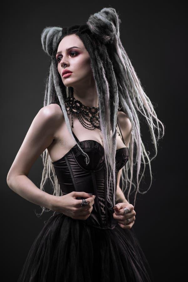 A mulher com teme e vestido gótico preto fotografia de stock
