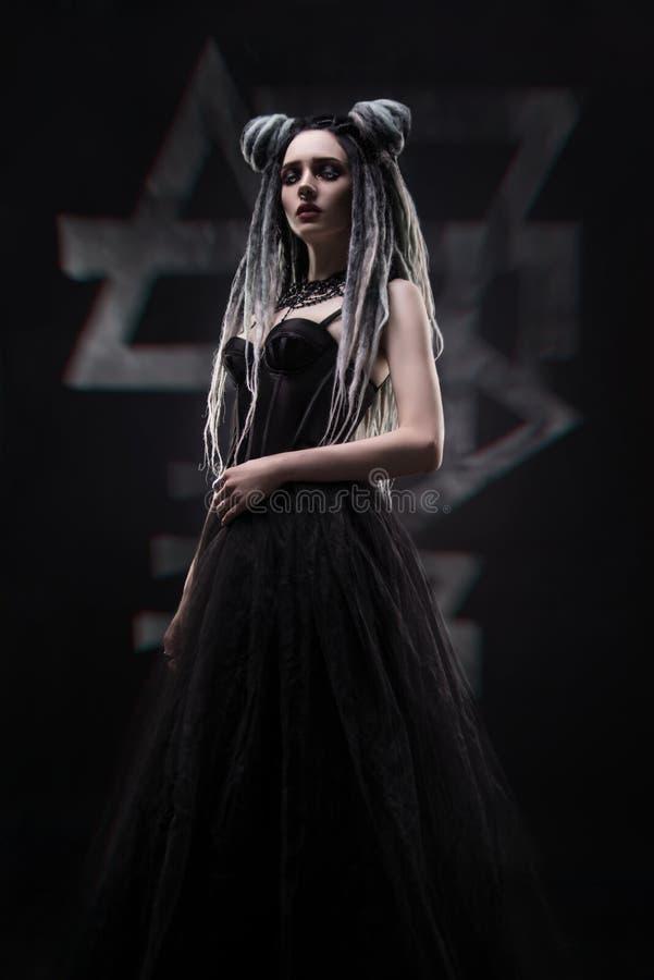 A mulher com teme e vestido gótico preto festivo foto de stock
