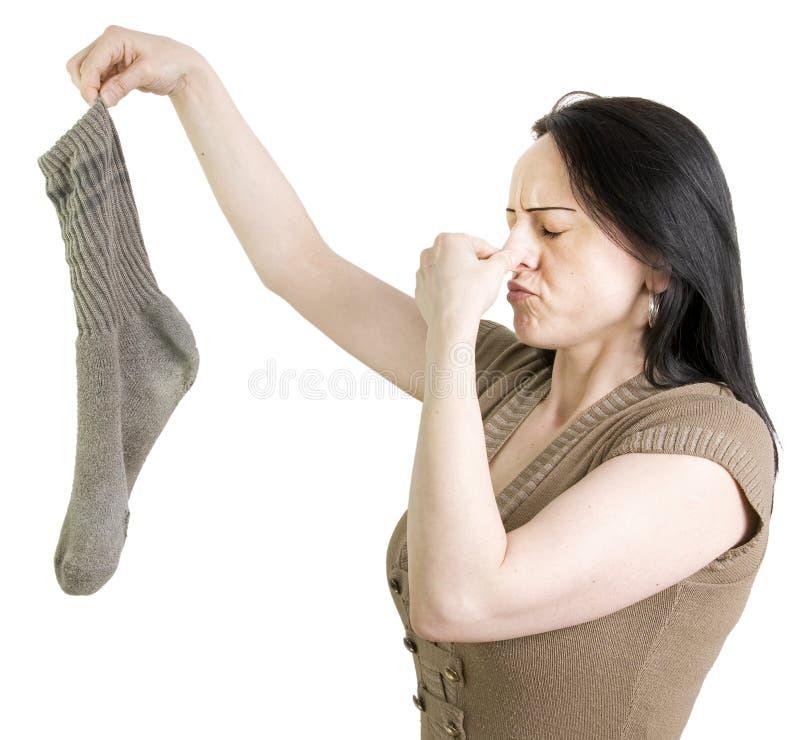 Mulher com terra arrendada suja da peúga seu nariz imagem de stock