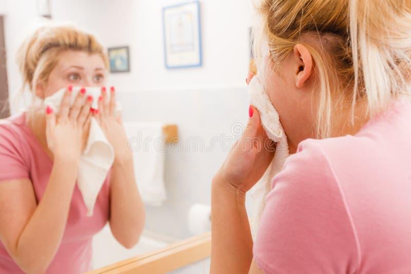 Mulher com a toalha branca que limpa a cara ap?s a limpeza fotografia de stock