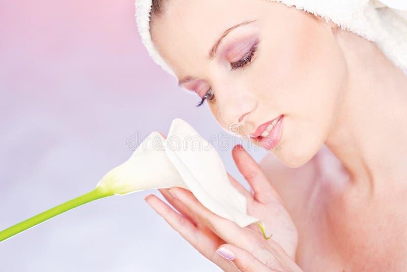 Mulher com a toalha que prende delicadamente a flor imagens de stock