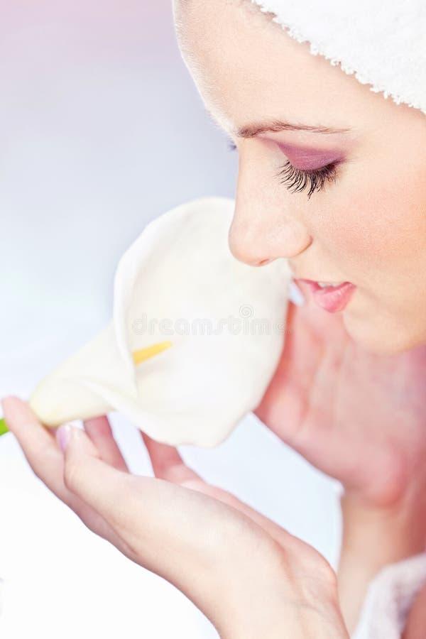 Mulher com a toalha que prende delicadamente a flor fotos de stock