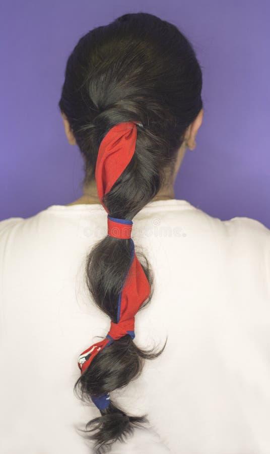Mulher com a trança decorada com uma curva vermelha foto de stock