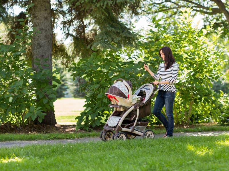 Mulher com transporte de bebê usando o telefone celular no parque imagens de stock royalty free