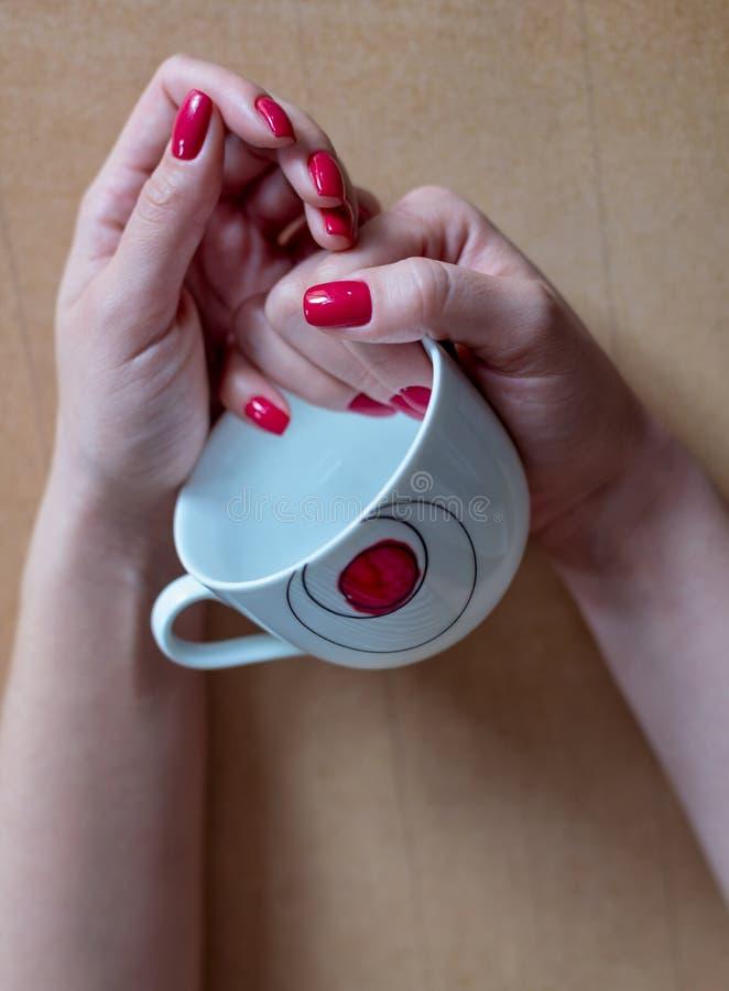 A mulher com tratamento de mãos vermelho guarda um copo de café vazio nela imagens de stock royalty free
