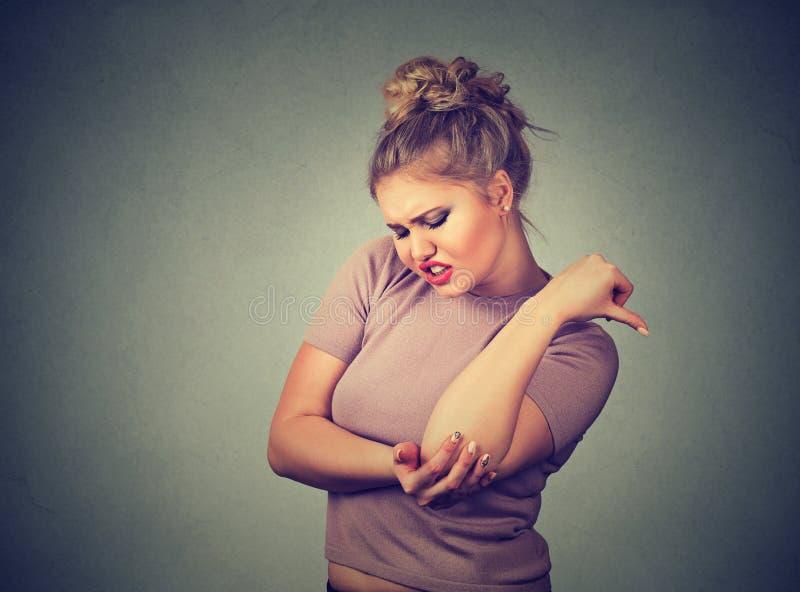 Mulher com traumatismo comum da inflamação O cotovelo da fêmea Dor e ferimento do braço fotografia de stock royalty free