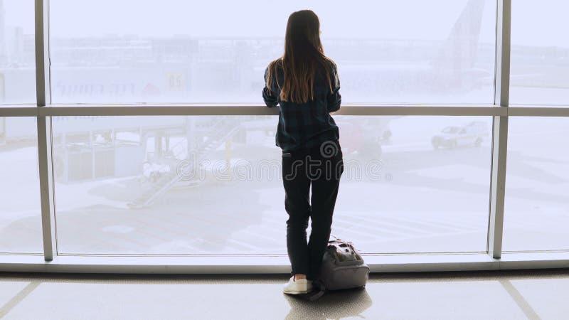 A mulher com trouxa anda à janela do aeroporto Menina europeia bem sucedida feliz do passageiro com o smartphone no terminal 4K imagem de stock
