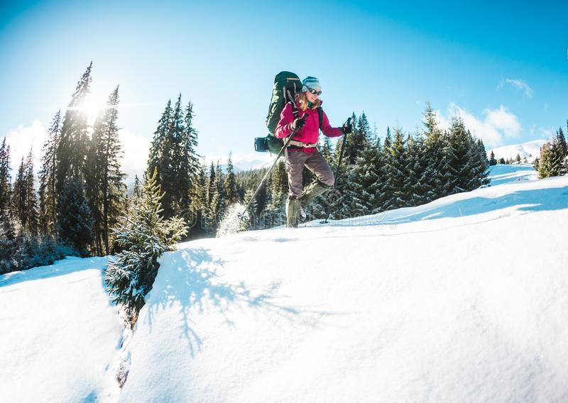 Mulher com trouxa e sapatos de neve nas montanhas do inverno imagens de stock