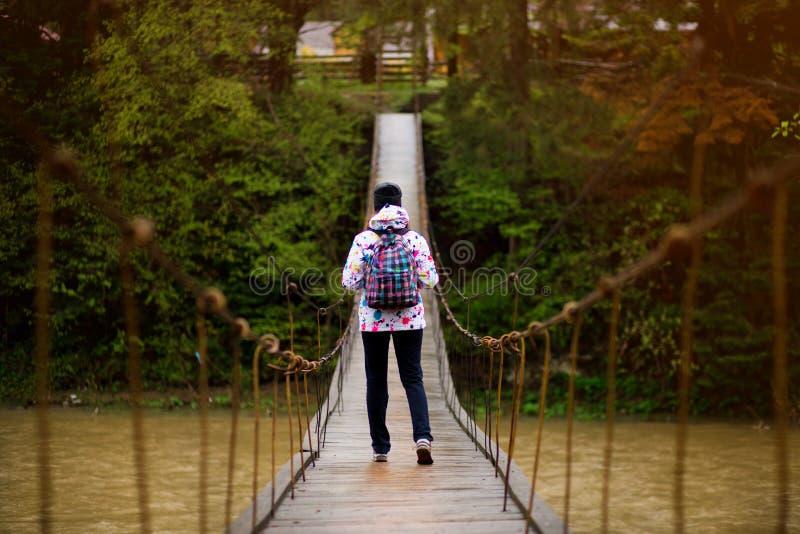 Mulher com a trouxa que caminha a floresta do conceito da aventura do estilo de vida e o rio transversal em férias ativas da flor fotografia de stock royalty free