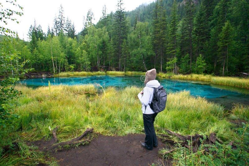 Mulher com a trouxa que caminha a floresta e o lago do conceito da aventura do estilo de vida fotografia de stock royalty free