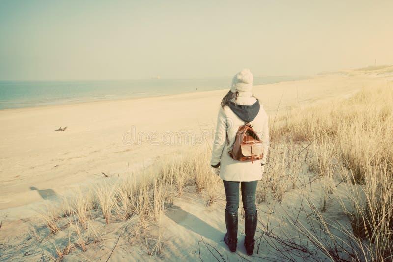 Mulher com a trouxa retro na praia que olha o mar imagens de stock royalty free