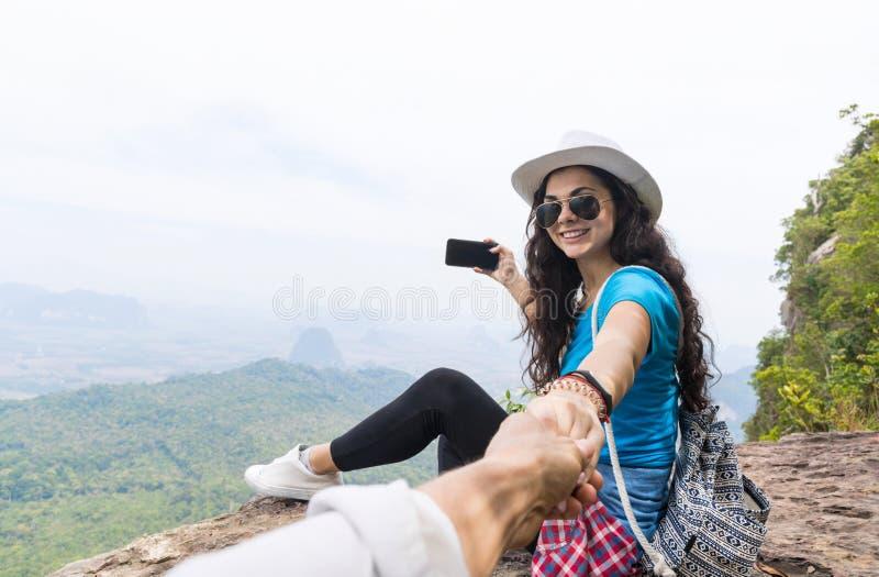 A mulher com trouxa toma a foto da paisagem da parte superior da montanha no telefone esperto da pilha que guarda a mão do homem fotografia de stock royalty free