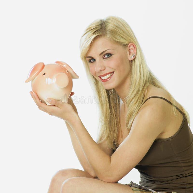 Mulher com um banco piggy fotografia de stock royalty free