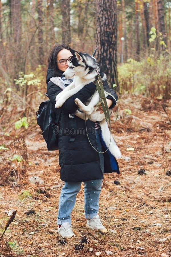 Mulher com um cão ronco no parque fotografia de stock royalty free