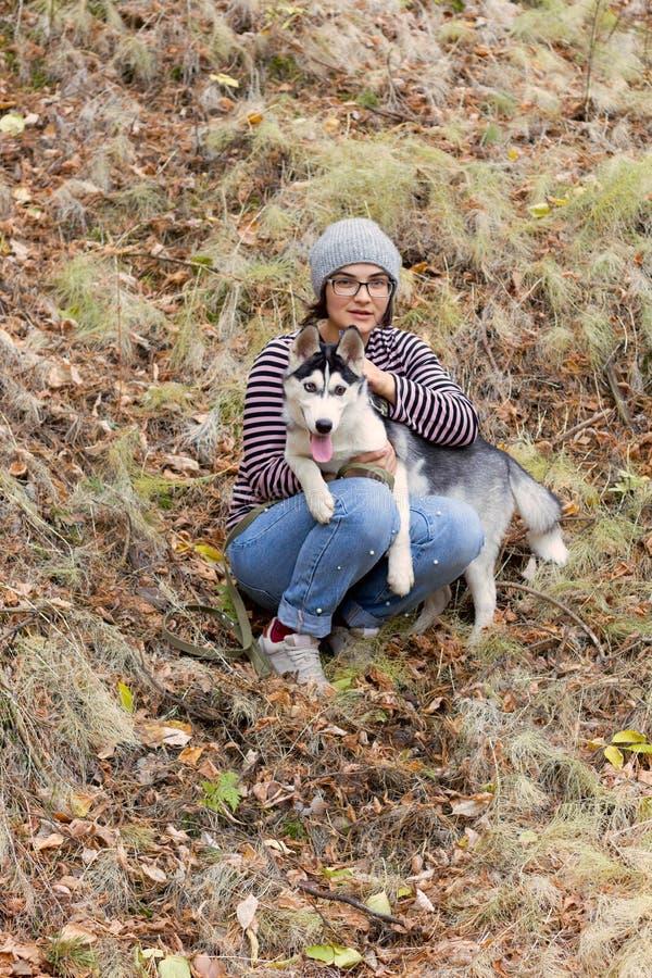 Mulher com um cão ronco no parque imagem de stock royalty free