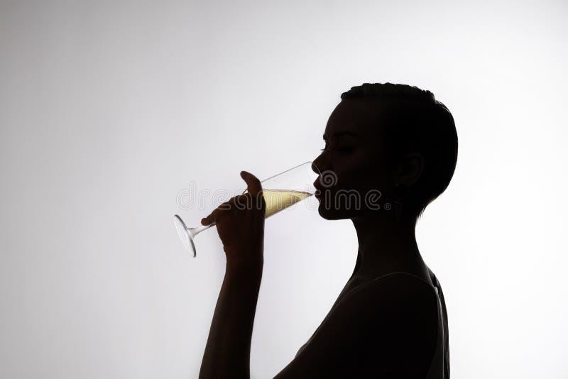 A mulher com um cabelo curto bebe o champanhe, lado-cara imagem de stock