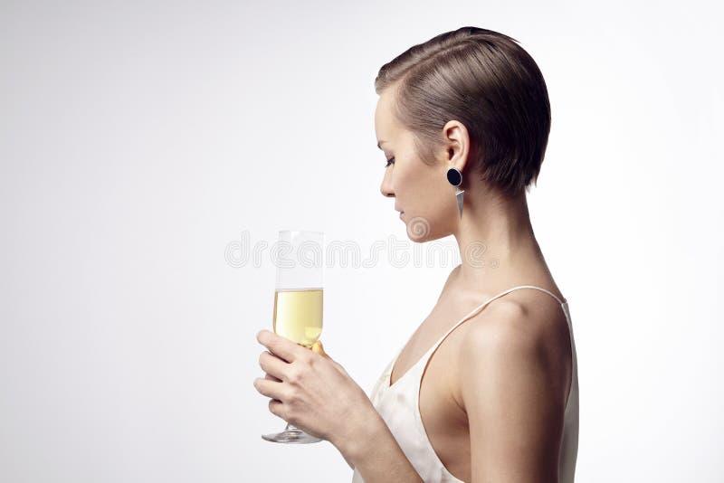 Mulher com um cabelo curto que comemora no partido com champanhe imagem de stock royalty free